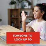 Young girl waving at mentor through computer screen